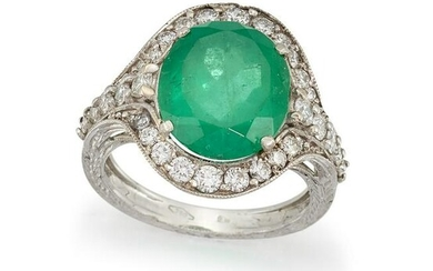 AN EMERALD AND DIAMOND CLUSTER RING The oval-cut
