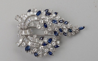 An 18 karat white gold brooch set with brilliant-cut diamonds and baguette-cut diamonds for a total of +/-15 carats and marquise cut sapphires for a total of +/-2.75 carats. Total weight:+/-23.55grs.