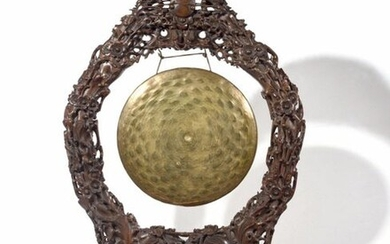 China or South East Asia GONG in embossed copper, the support in carved and openwork wood with complex patterns of prunus branches in bloom. XIXth century Height: 100 cm, Width: 64 cm (some lacks, cracks and pieces to be glued together)