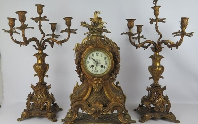 Gilded bronze mantel set with rocaille decoration and a man's mask comprising a clock and a pair of five-light candelabra.