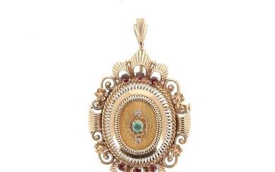 Oval brooch or pendant in 18 K(750°/°°) yellow gold with chased and stamped decoration presenting openwork volutes. In the center, an emerald surrounded by two faceted diamond chips, on each side, three brown-red garnets.