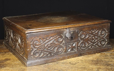 A 17th Century Desk Box. The moulded lid on iron strap hinges. The front carved with arabesque strap