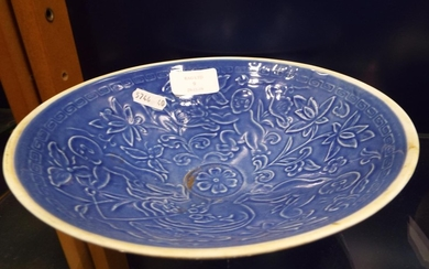 A Chinese blue glazed bowl decorated with figures amongst bl...