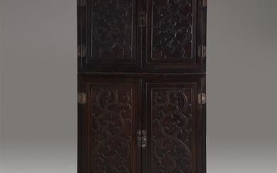 A Chinese carved hardwood two-part compound cabinet The doors...