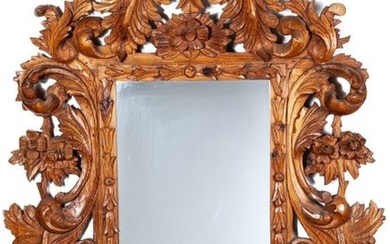 A carved wooden mirror in the Baroque style,...