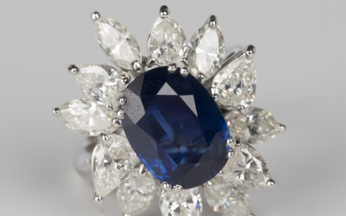 A sapphire and diamond ring, claw set with the oval cut sapphire within a surround of twelve alterna