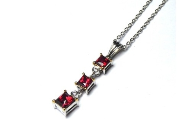 AN 18CT WHITE GOLD, RUBY AND DIAMOND PENDANT Three graduated...