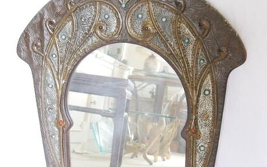 Arched mirror in a rich frame in slight relief of repoussé brass and pewter plants with blue glass cabochons.