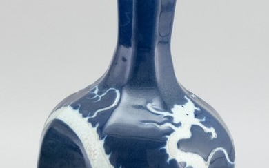 """CHINESE WHITE-ON-BLUE PORCELAIN VASE Octagonal, with a white dragon and pearl design on a blue ground. Height 12.7""""."""