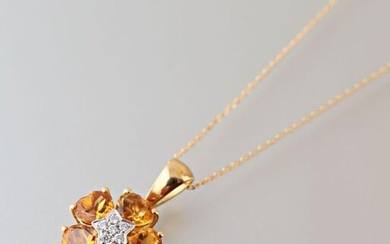 Pendant and its chain in 750 thousandths yellow gold, the flower-shaped pendant is decorated in its center with a star paved with modern cut diamonds, the petals set with five heart-shaped citrine.