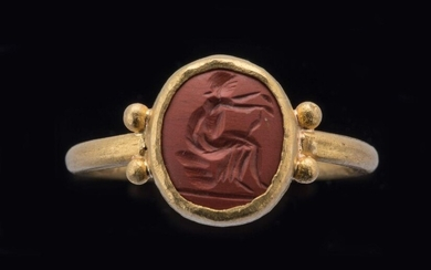 ROMAN INTAIL in red jasper depicting a seated woman. Mounted on a gold ring. Two gold globules adorn the shoulders where the ring attaches to the bezel. 3rd-5th c. A.D. Height intaglio 10, Width 18 mm. Finger circumference: 57. Gross weight : 6 g...