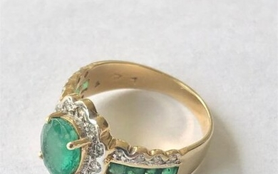 Yellow and white gold 750 thousandths ring set with an oval emerald netted with brilliants in the center shouldered by two lines of calibrated emeralds and four lines of brilliants 4 g, size 51 - Emerald 7.6 x 5.9 x 3.7 mm or about one carat.