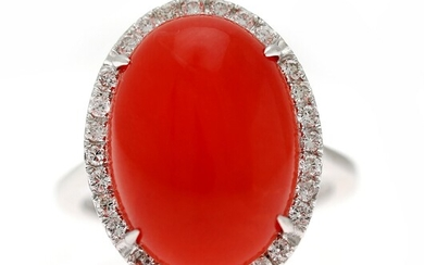 NOT SOLD. A coral and diamond ring set with a cabochon coral encircled by diamonds,...