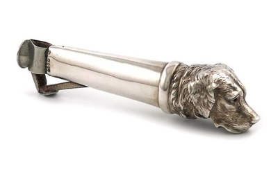A late-Victorian novelty silver cigar cutter, with import marks for London 1899, importer~s mark of Theodor Hartmann, tapering handle, the terminal modelled as the head of a Labrador dog, set with red eyes, length 13.7cm. Provenance: The late Greta...