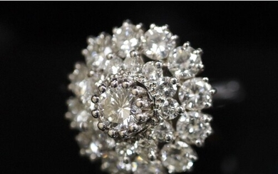 A modern 14ct white gold and diamond cluster ring, the centr...