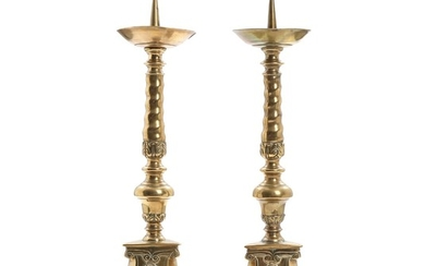 A pair of Baroque style brass spike tip candlesticks, triangular base, raised on paw feet. 19th century. H. 57 cm. (2)
