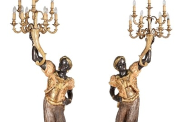 A pair of carved, painted, ebonised and parcel gilt wood blackamoor torcheres