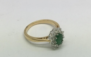 An 18ct gold oval cut emerald and diamond cluster ring. Emer...