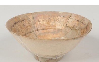 An antique Islamic pottery bowl. Buff ground and with styliz...