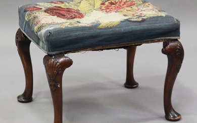 An early 20th century Queen Anne style walnut stool, raised on shell-carved cabriole legs and pad fe