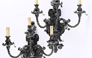 An important pair of wrought iron wall lights, the cut-out plate with scrolling motifs and acanthus leaves supports three twisted arms of lights underlined with motifs in reminder