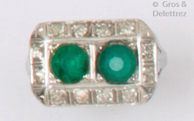 A chased white gold ring set with two green stones in a ring of old cut diamonds. Art Deco period work. Finger size : 53. P. Brut: 6.4g. (One stone missing)