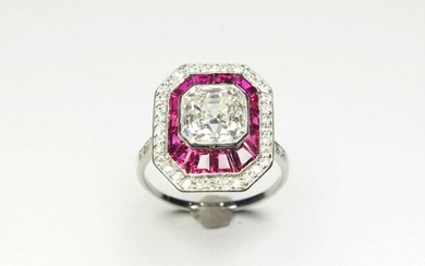 Platinum ring (850/oo), the octagonal plate centered with a square shaped emerald cut diamond calibrating approximately 3.05 carats, colour assumed J/K, SI clarity, set in a double surround of calibrated rubies and 8x8 cut diamonds. Diamond...