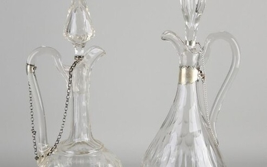 Two crystal carafes with silverware, 833/000, carafes with cut, placed on a round base with pearl edging and a silver chain attached to the stopper and the carafe. ø14x39cm and ø14x42cm. 1 chip at the stop. In good condition