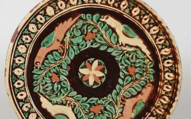 A Bombay School of Arts pottery charger. Decorated with bird...