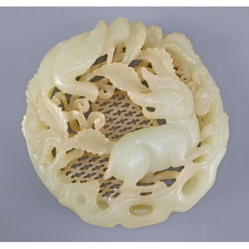 A Chinese pale celadon jade circular plaque, carved in relie...