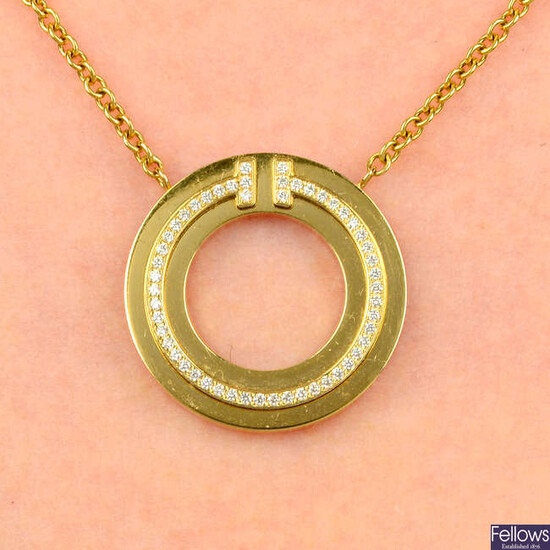 A diamond 'T' circle pendant, by Tiffany & Co., later applied to a belcher-link chain, by Fope.