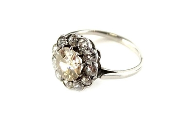 A diamond daisy cluster ring, with central round brilliant...