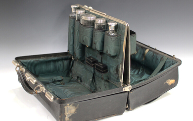 An Edwardian black leather Gladstone vanity bag, the interior fitted with five silver and cut glass