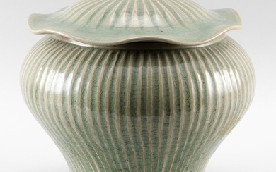 """CHINESE CELADON STONEWARE COVERED JAR In inverted pear form, with lotus leaf-form cover and ribbed body. Height 10"""". Diameter 10.5""""."""