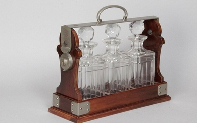 ENGLISH WHISKY CELLAR THE TANTALUS, in mahogany and metal with three carved glass decanters and their stoppers, from Maison BETJEMANN London. With these keys. H: 29 x W: 36 x D: 13 cm