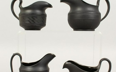 FOUR VARIOUS BLACK BASALT MILK JUGS.