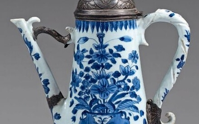 Large Chinese porcelain ewer with silver frames. Kangxi porcelain (1662-1722), 950°/°° silver mounts, foreign work probably from the 19th century. Truncated cone shape, with blue-white decoration on each side of a vase of flowers placed on rocks, some...