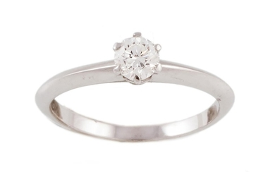 A DIAMOND SOLITAIRE RING, signed Tiffany & Co, with one roun...
