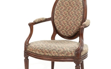 A French walnut Louis XVI armchair, curved armrests, fluted legs. Late 18th century.