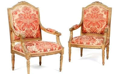 A PAIR OF GILTWOOD FAUTEUILS IN LOUIS XVI STYLE LATE 19T CENTURY each with a padded back, seat and armrests, covered in damask fabric, the moulded frames carved with leaves and flowers (2)
