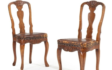A pair of 18th century elmwood Rococo chairs carved with mussels and foilage, upholstered with patinated studded leather. (2)