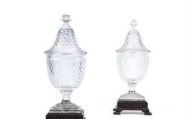 A pair of large Continental cut-glass urns, domed covers and associated carved wood stands, 20th century