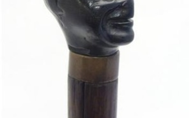 A walking stick / cane with a carved ebonised pommel