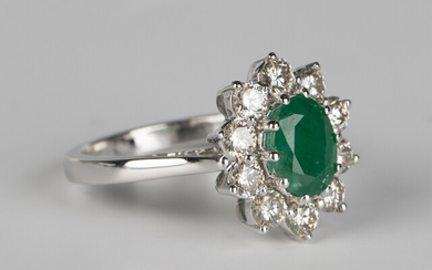 A white gold, emerald and diamond cluster ring, claw set with an oval cut emerald within a surround