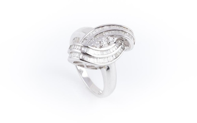 AN 18CT WHITE GOLD DIAMOND DRESS RING; centring 3 graduated round brilliant cut diamonds to double surround of channel set baguette...