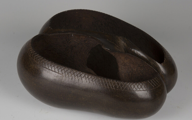 An early 20th century coco-de-mer nut, carved as a two-section bowl with central handle, length 27cm