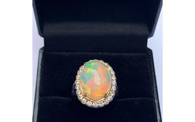 An opal and diamond cluster ring, the central oval natural o...