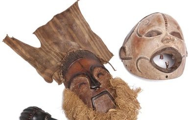 Three masks of carved patinated wood, one mounted with raffia and cloth, traces of black and white pigment. Bassa, Igbo and D. R. Congo style. H. 19–32 cm. (3)