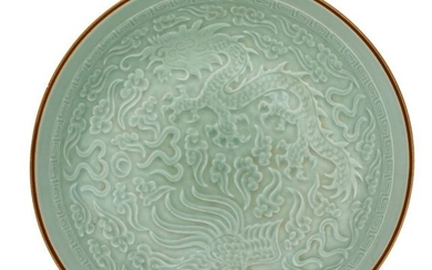 A Chinese celadon-glazed dish, relief decorated with a...