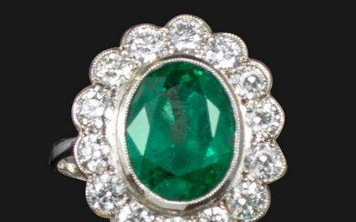 An emerald and diamond cluster ring, centred with an oval-shaped emerald within a surround of round brilliant-cut diamonds in platinum, size O 1/2